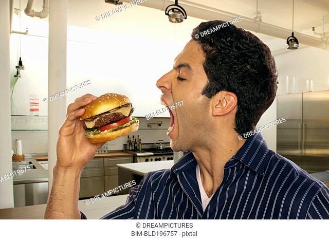 Hispanic man eating hamburger