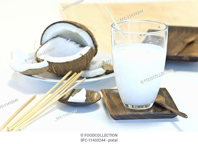 A glass of coconut milk and a broken coconut