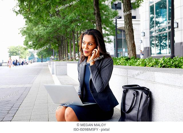 Businesswoman using cellphone and laptop on street seating
