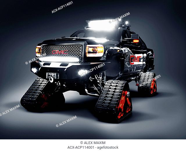 GMC pickup truck outfitted with Mattracks rubber snow tracks instead of wheels isolated on gray studio background with clipping path