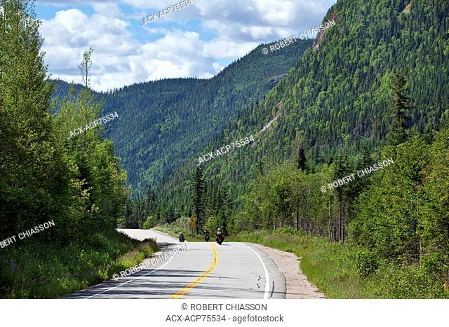Motocyclists touring on a road that cuts through a mountain range in Parc national des Grands-Jardins, Charlevoix, Quebec, Canada