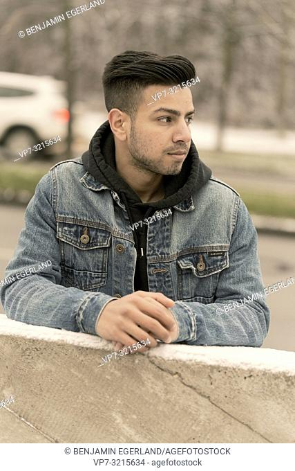 Portrait of young man leaning on railing at street in city, pensive mood, in Munich, Germany. Afghan ethnicity