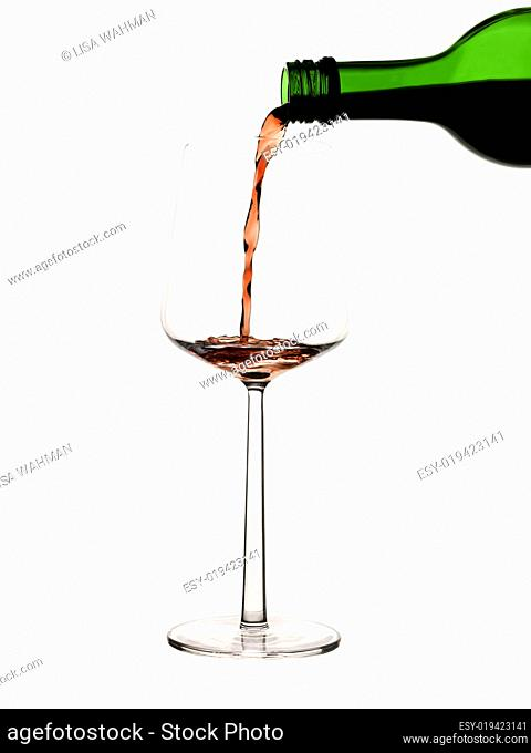 Puting red wine bottle to the glass