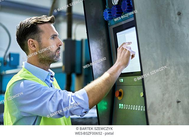 Engineer using computer and operating machinery in factory