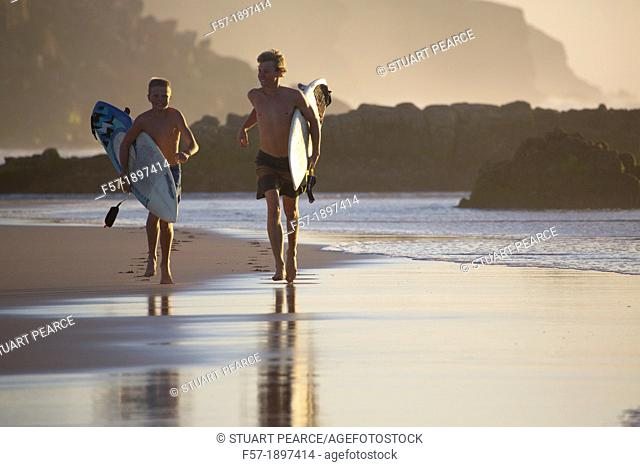 Two young surfers on Cotillo beach in Fuerteventura, Spain