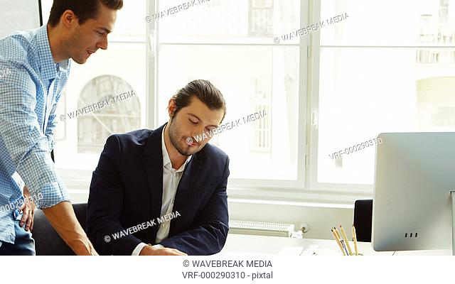 Business colleagues discussing on blueprint
