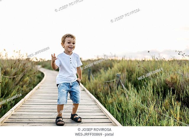 Happy little boy standing on boardwalk in nature