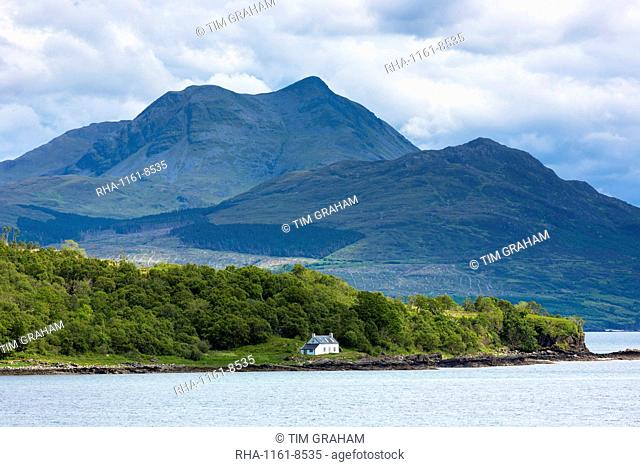 Solitary whitewashed croft cottage across the Sound of Sleat with Knoydart mountain behind, Isle of Skye, Inner Hebrides and Western Isles, Scotland