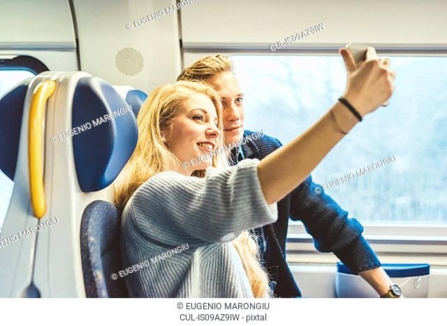 Young couple taking smartphone selfie in train carriage