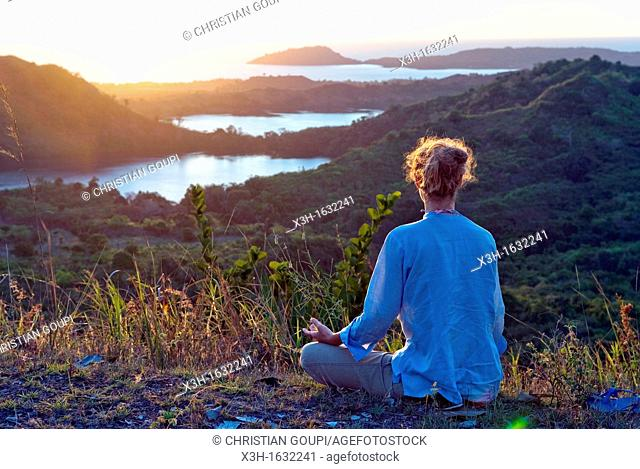 young woman relaxing on Mount Passot at sunset, Nosy Be island, Republic of Madagascar, Indian Ocean