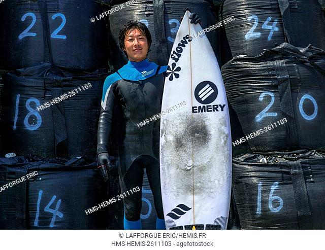 Japan, Fukushima Prefecture, Tairatoyoma Beach, japanese surfer in front of bags with contaminated sand after the daiichi nuclear power plant irradiation