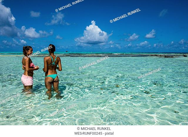 Carribean, Colombia, San Andres, El Acuario, two women standing in shallow turquoise water