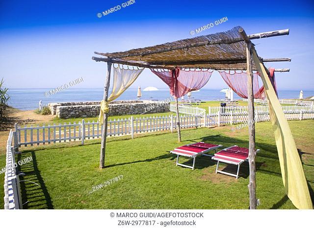 Small summer gazebo built with wooden poles and canes