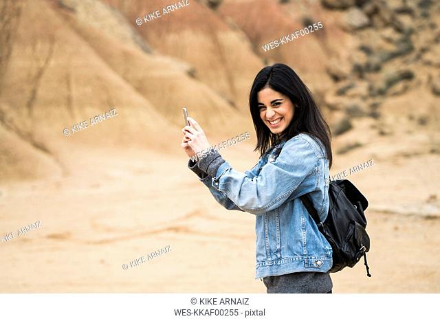 Spain, Navarra, Bardenas Reales, laughing young woman in nature park taking selfie with cell phone