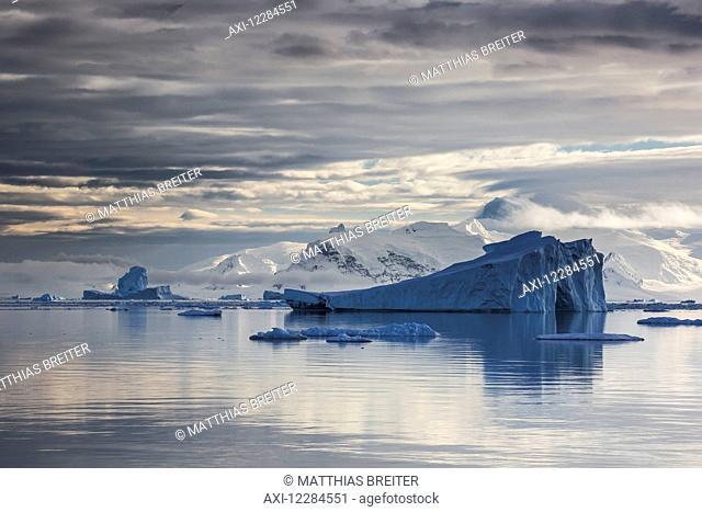 Iceberg in Gerlache Strait in front of glaciated peaks on Antarctic Peninsula; Antarctica