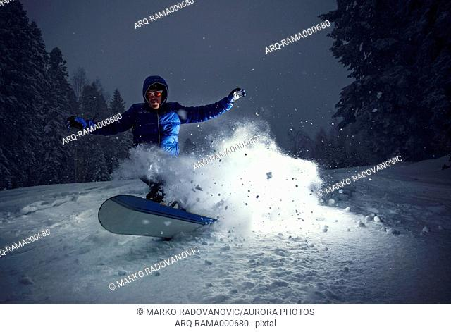 Snowboarder in turn in deep snow on the mountain Goc, Serbia. Shot lit by strobe
