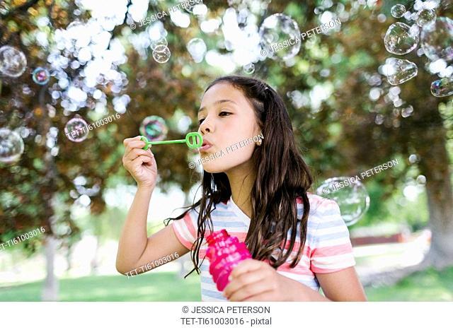 Portrait of girl ( 10-11 ) blowing soap bubbles