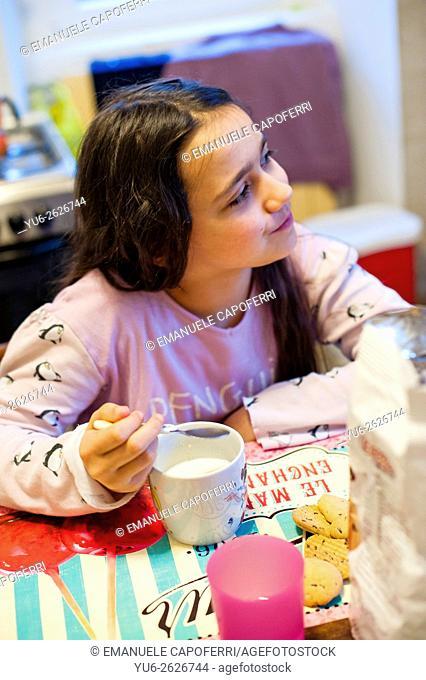 Little girl eat milk with breakfast biscuits