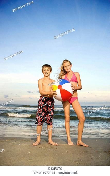 Caucasian pre-teen boy and girl holding beachball on beach