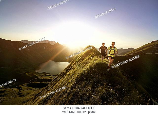 Germany, Allgaeu Alps, man and woman running on mountain ridge