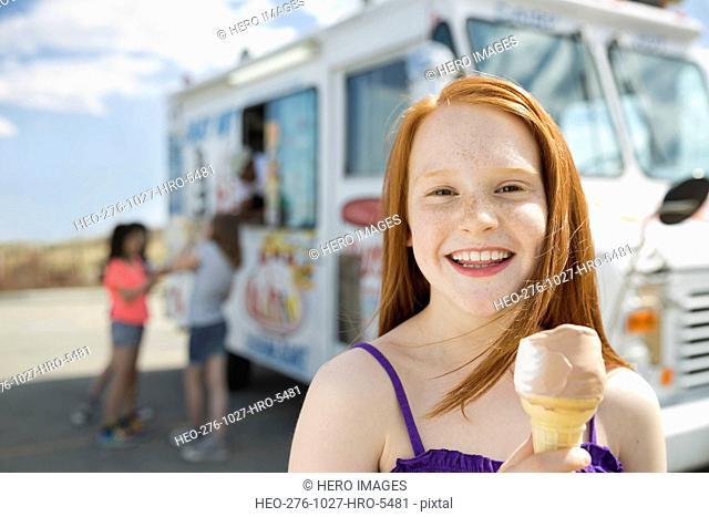 Portrait of cheerful girl holding ice cream cone against van