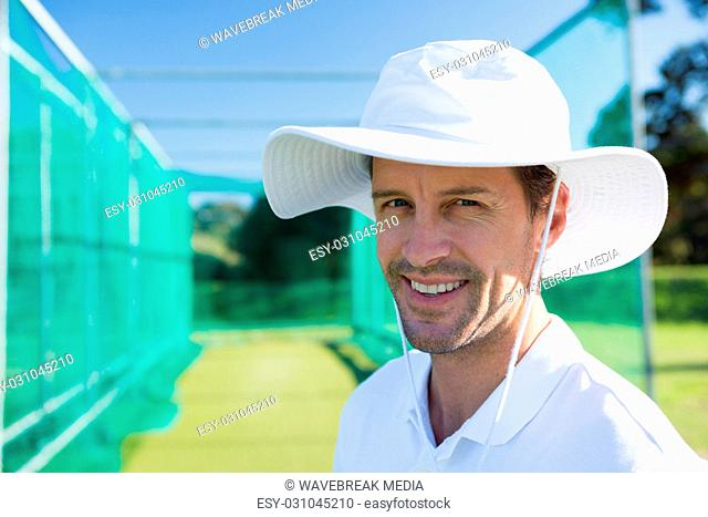 Portrait of smiling cricketer standing at field