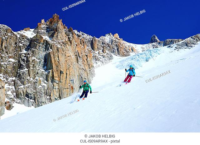 Male and female skiers skiing down Mont Blanc massif, Graian Alps, France