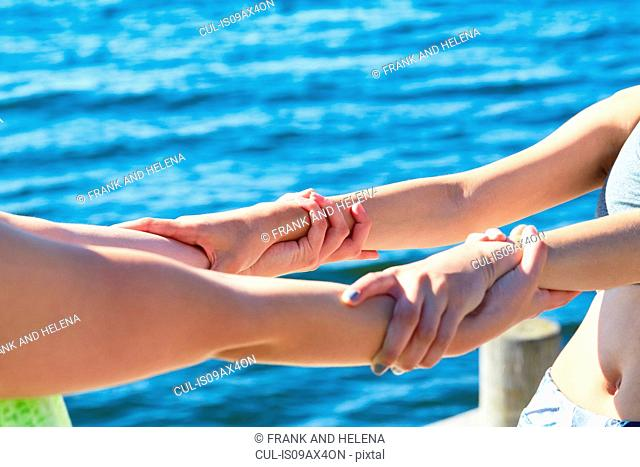 Cropped view of women in front of ocean holding into each others wrists