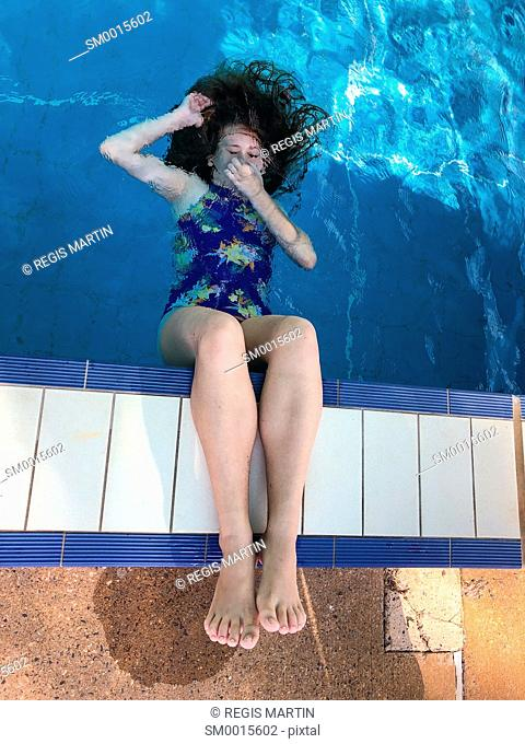 Girl playing holding her breath under water at the edge of a swimming pool