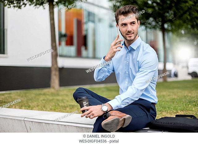 Smiling businessman sitting outdoors with cell phone and takeaway coffee