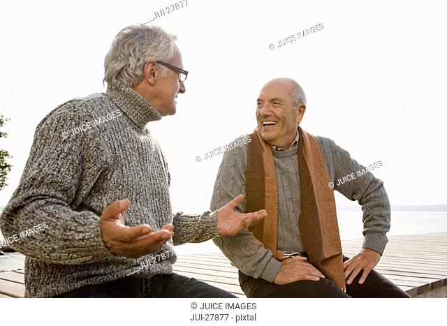 Two senior men sitting on a wooden jetty, talking to each other