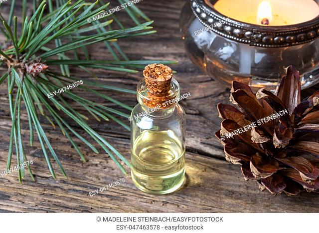 A bottle of essential oil with fresh pine branches