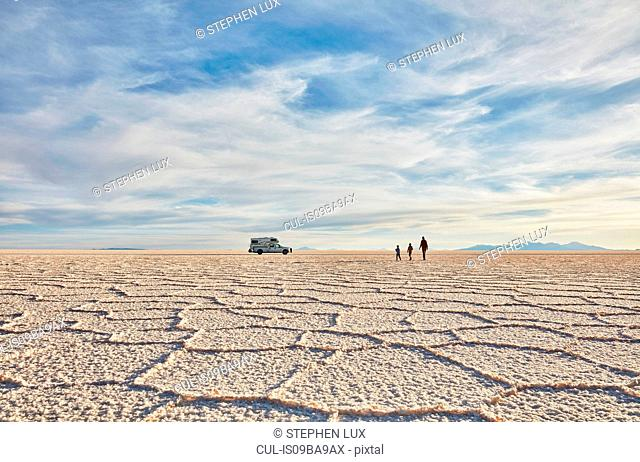 Mother and sons walking across salt flats, recreational vehicle in background, Salar de Uyuni, Uyuni, Oruro, Bolivia, South America