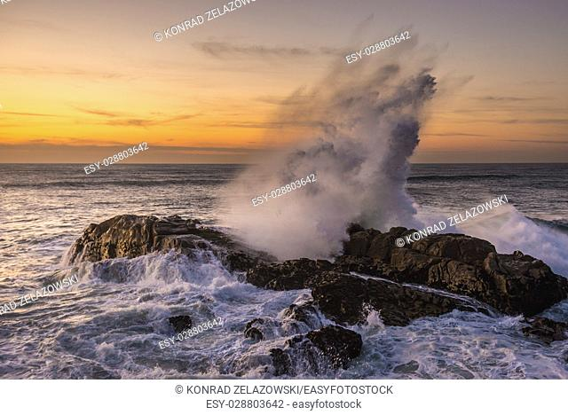 Atlantic Ocean waves crashing on rocks. View from breakwater of Foz do Douro district of Porto city, second largest city in Portugal