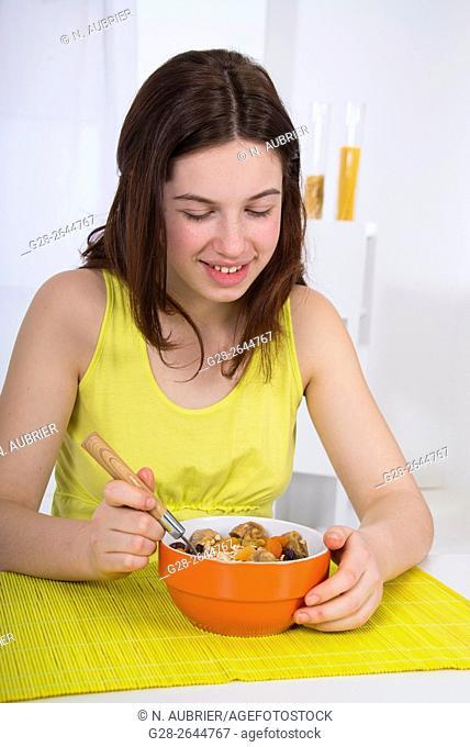 Teenage girl eating muesli for breakfast