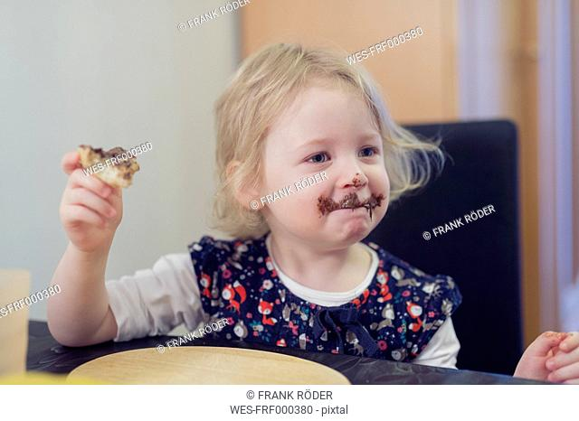 Portrait of little girl with nut-nougat cream on her face
