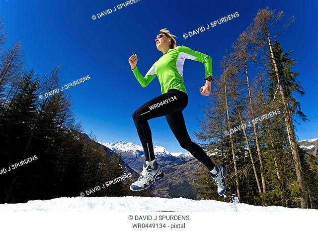 A woman jogging through snowy winter mountains