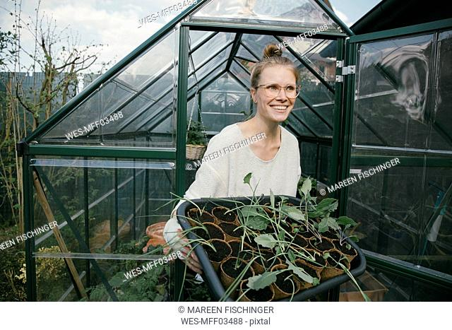 Portrait of happy young woman with potted seedlings in front of greenhouse
