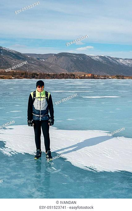 Traveler standing on the ice of Lake Baikal. Equipment for the cycling part, for cold weather. On his back hangs a bicycle backpack, sports gloves on his hands