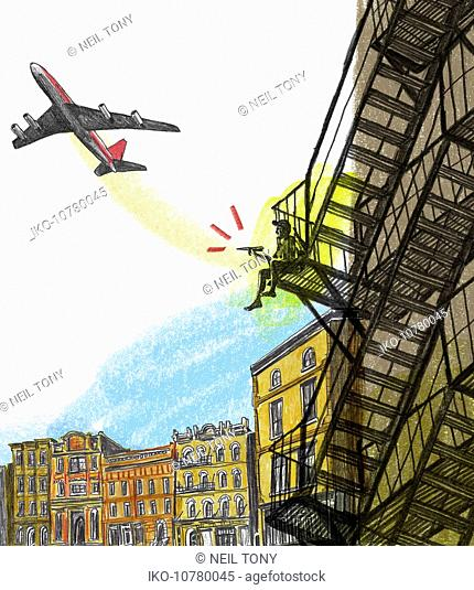 Boy sitting on fire escape with paper airplane watching airplane flying