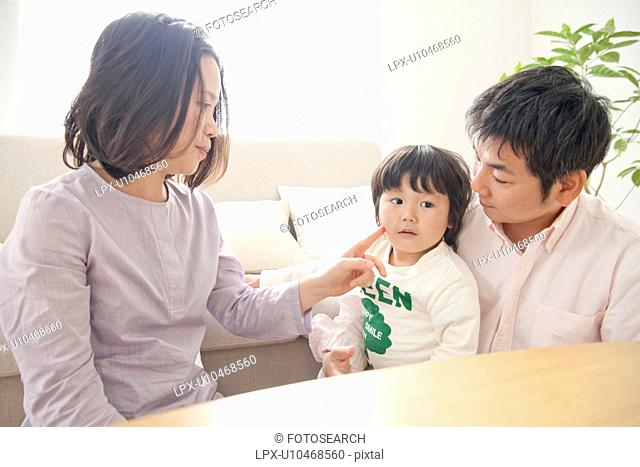 Family of three in living room