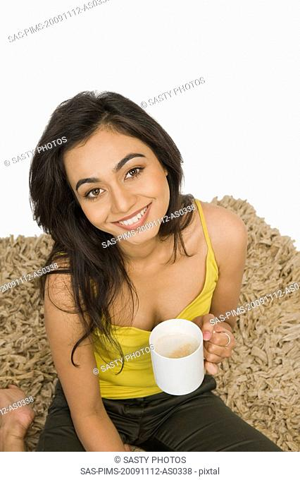 Portrait of a woman sitting on a rug and holding a coffee cup