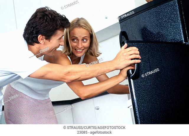 Caucasian couple looking in fridge together