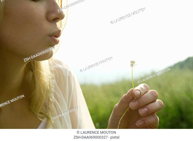 Young woman blowing dandelion seedhead
