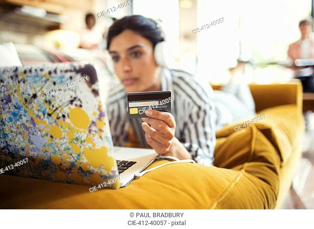 Young woman with headphones and credit card online shopping at laptop on living room sofa