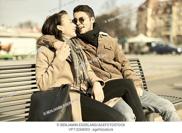 young teenage couple sitting together on bench in city, looking at each other, in Cottbus, Brandenburg, Germany