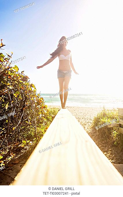 Young woman balancing on boardwalk