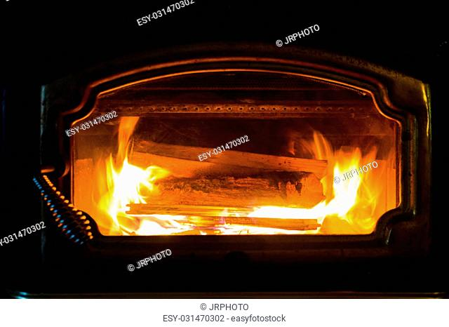Burning wood in a fireplace in the winter with orange flames