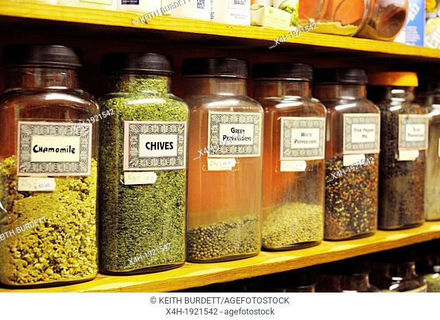 Jars of dried herbs and spices on shelves in a health food shop, Wales