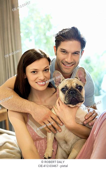 Couple hugging dog on bed
